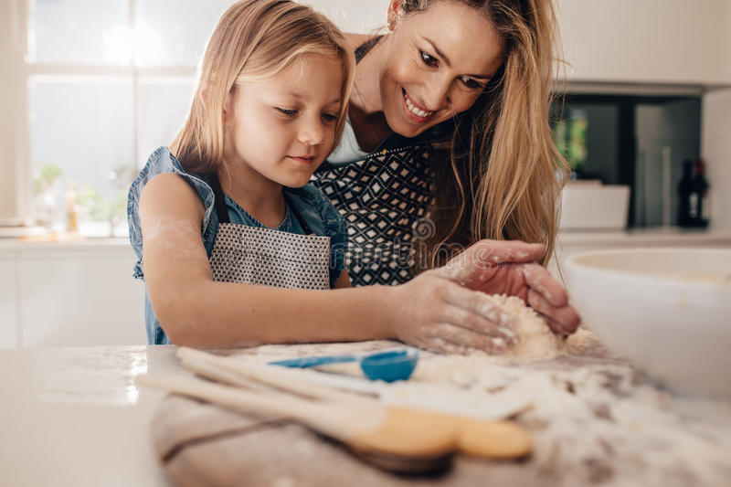 Mother teaching her daughter to make dough royalty free stock photo
