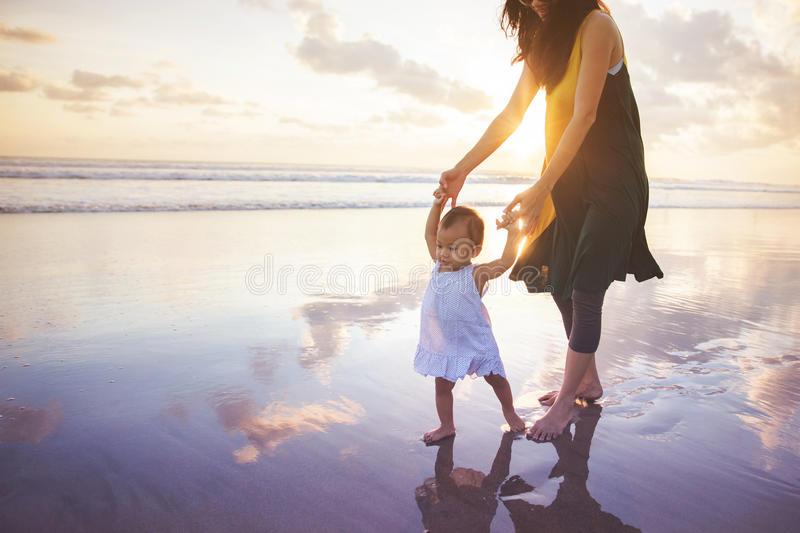 Mother is teaching her daughter walks on the beach stock photography
