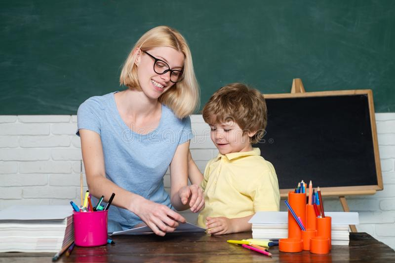 Mother teaching her son in classroom at school. Funny little child and young female teacher having fun on blackboard stock photos