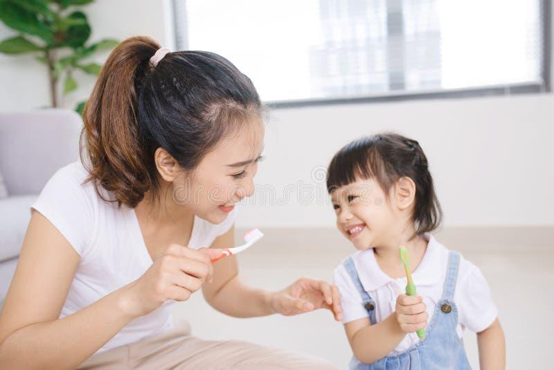 Mother teaching kid daughter teeth brushing at home.  royalty free stock images