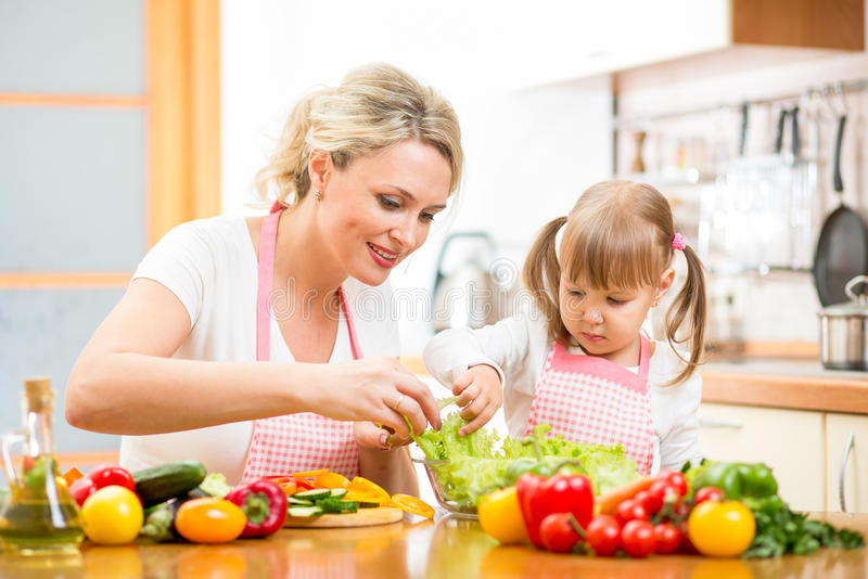 Mother teaching kid daughter to cook stock photos