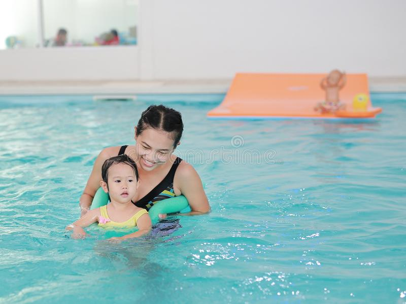 Mother teaching kid in swimming pool with foam noodle royalty free stock photos