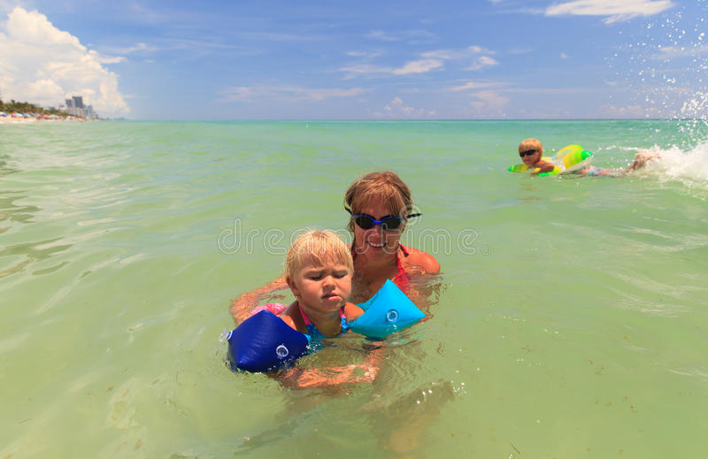 Mother teaching little daughter to swim at sea stock photography