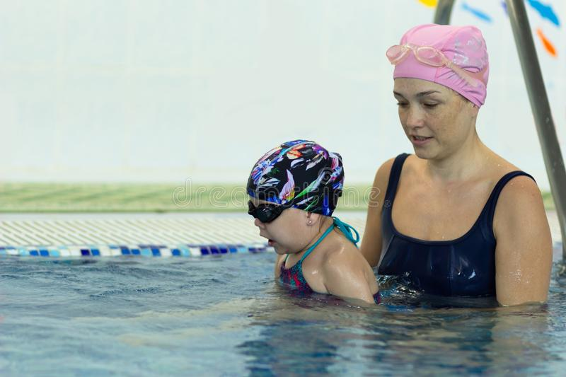 Mother teaching little girl to swim in the swimming pool royalty free stock photo