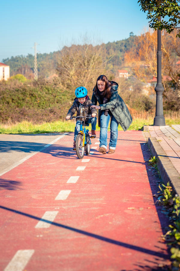Mother teaching son to ride a bike in cycleway royalty free stock photography