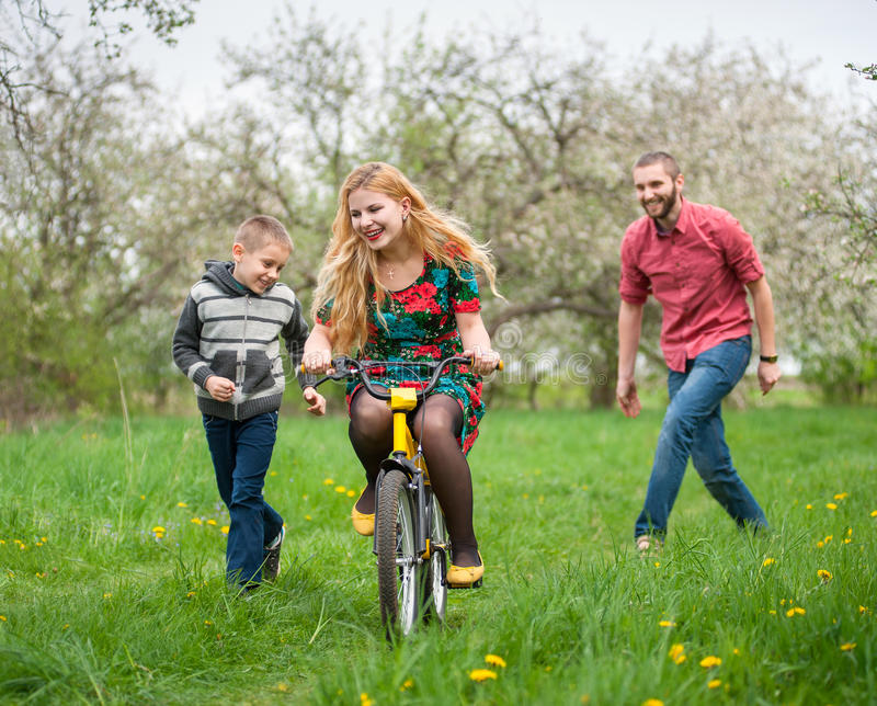 Mother teaching son to ride a bike by his example royalty free stock images