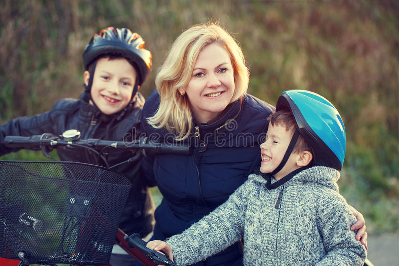 Mother teaching sons cycling. Outdoor activity stock photo