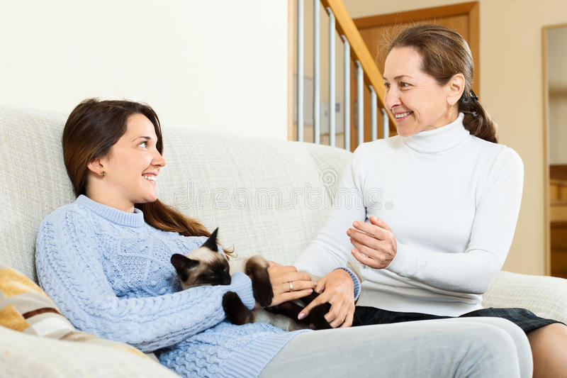 Mother and teen daughter discussing something on sofa. At home royalty free stock images