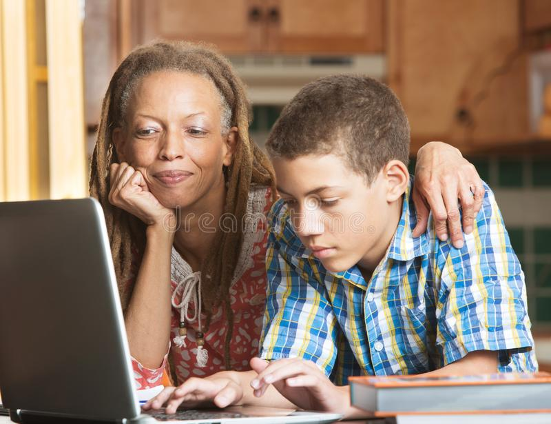 Mother and teen son work in kitchen on laptop royalty free stock images