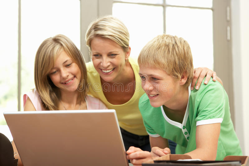 Mother And Teenage Children Using Laptop At Home stock image