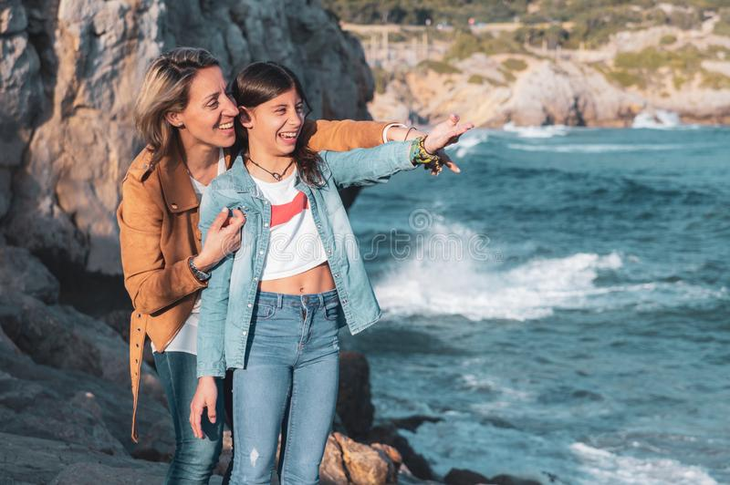 Mother and teenage daughter laughing and pointing to something in the Mediterranean Sea stock photos