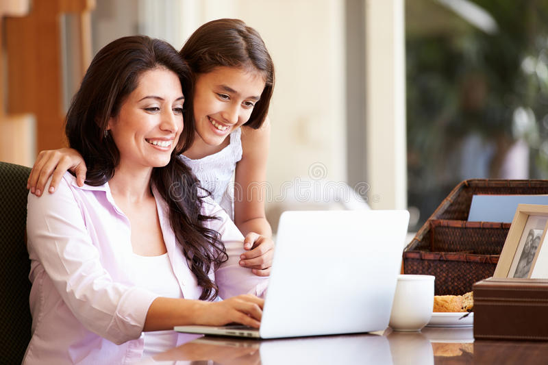 Mother And Teenage Daughter Looking At Laptop Together. At Home Smiling stock image