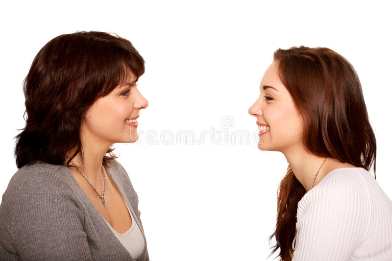 Mother and teenage daughter talking and laughing together. Happy family. A side view. Isolated on white background royalty free stock images