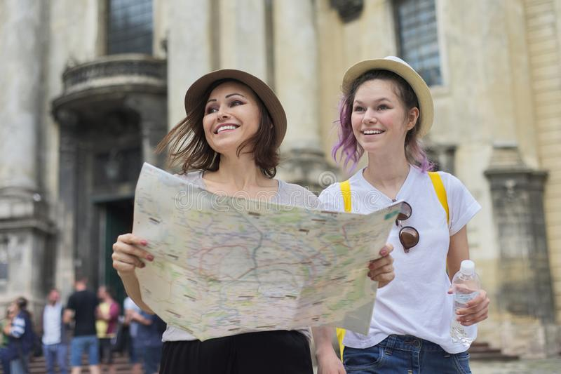 Mother with teenage daughter travel, women with map stock images