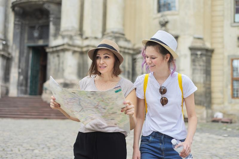 Mother with teenage daughter travel, women with map stock photography