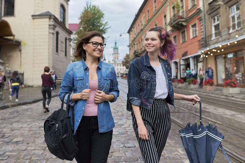 Mother and teenage daughter walking on city street. Talking and smiling royalty free stock photos
