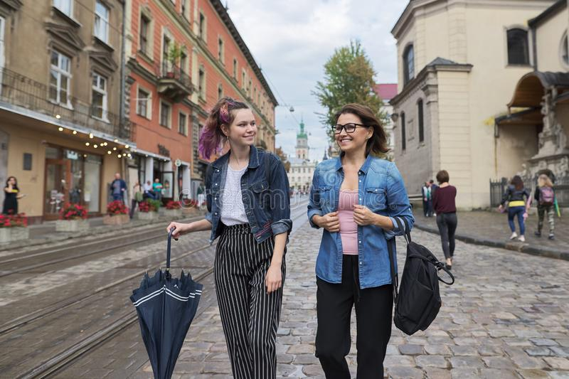 Mother and teenage daughter walking on city street. Talking and smiling stock photography
