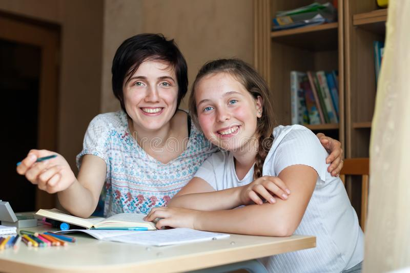 Mother and teenager daughter doing homework royalty free stock photos