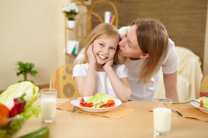Mother with teenager daughter having meal at home stock images