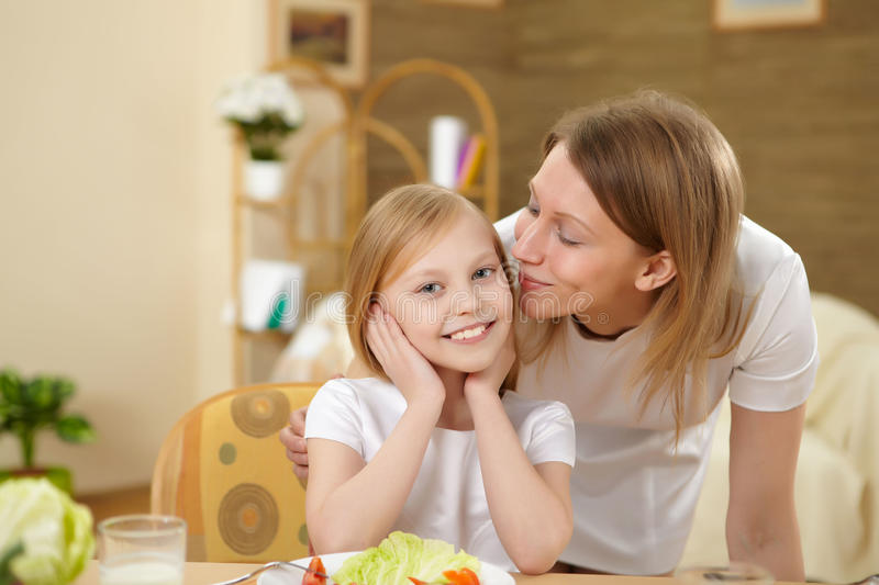 Mother with teenager daughter having meal at home. A teenaged daughter with her mother in th ekitchen at home having meal together stock photos