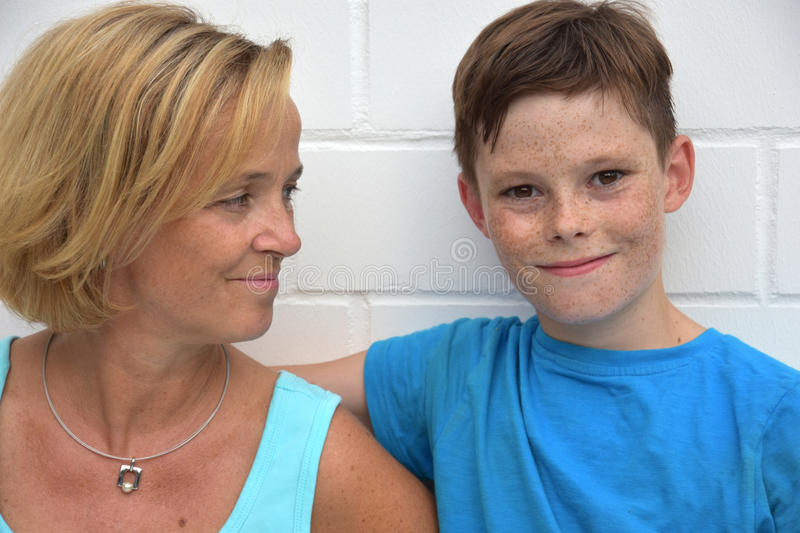 Mother and teenager son. Teenager son embracing his mother royalty free stock images