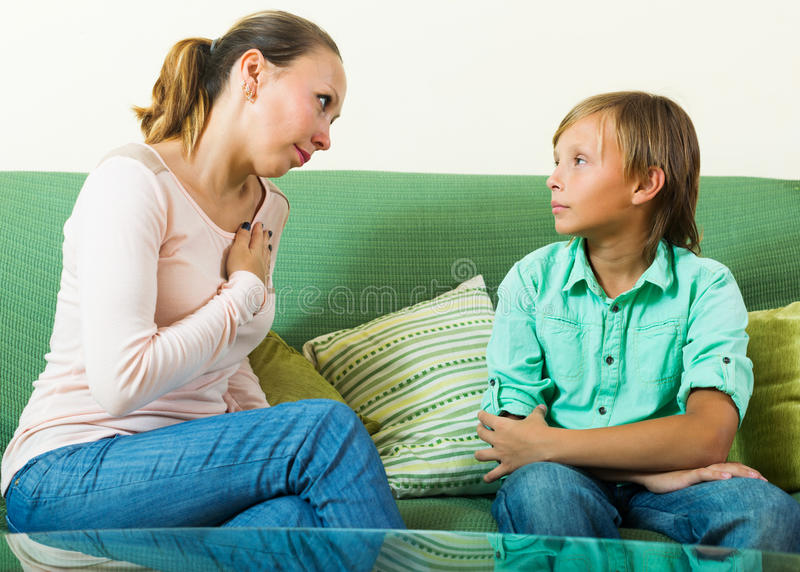 Mother with teenager son having serious conversation stock image
