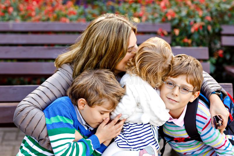 Mother and three children hugging. Happy family sitting outdoor: woman and two brother kids boys and cute little toddler stock images