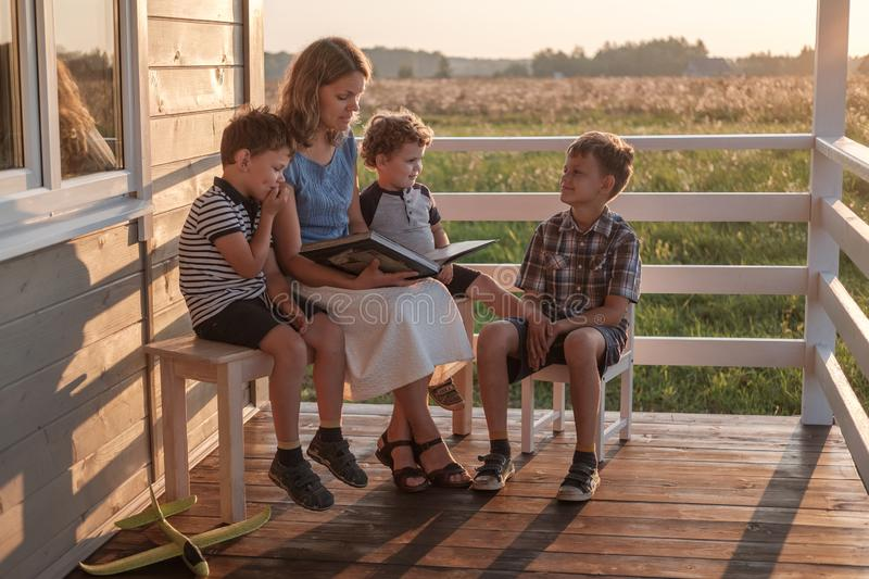 Mother with three children reading a book on the summer terrace of a country house royalty free stock photo