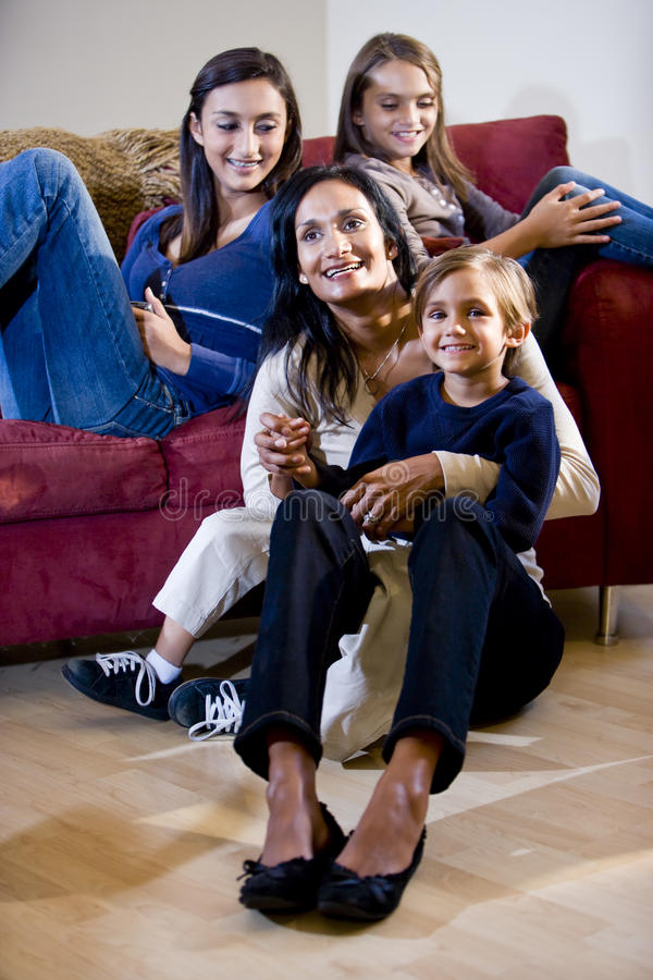 Mother with three children relaxing on living room. Indian mother with three mixed-race children relaxing on living room sofa, single mom stock images