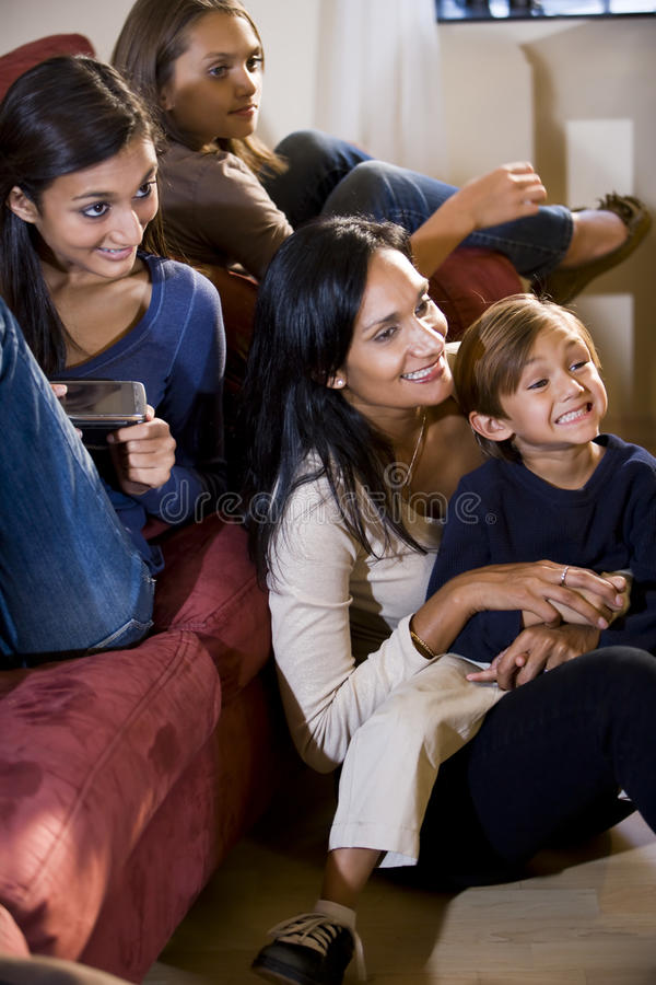 Mother and three children sitting together on sofa. Mother and three children sitting together on living room sofa watching television, single mom stock photo