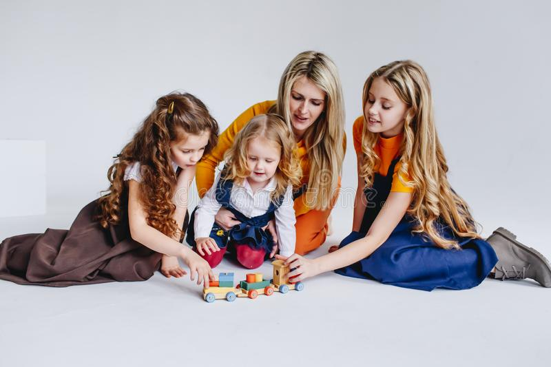 A mother with three cute daughters playing with wooden toy train. A family of four. concept of big family stock images