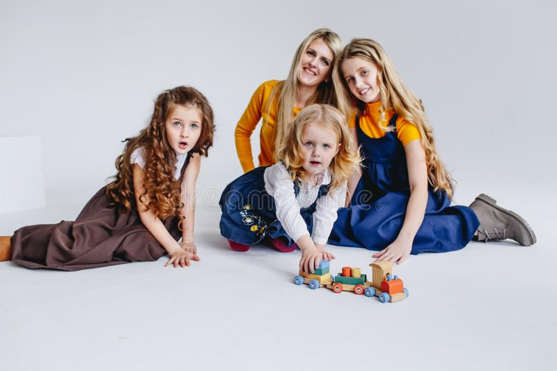 A mother with three cute daughters playing with wooden toy train. A family of four royalty free stock photo