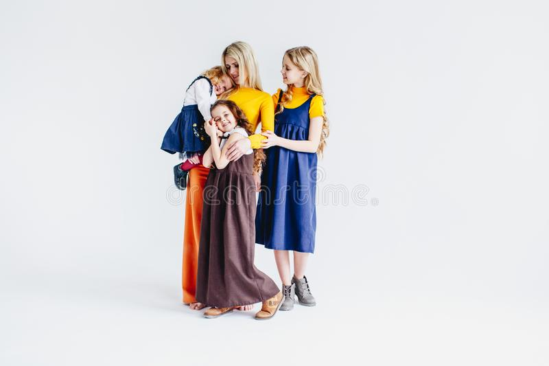 A mother with three cute daughters playing with wooden toy train. A family of four girls. Girls hugging their mother royalty free stock images