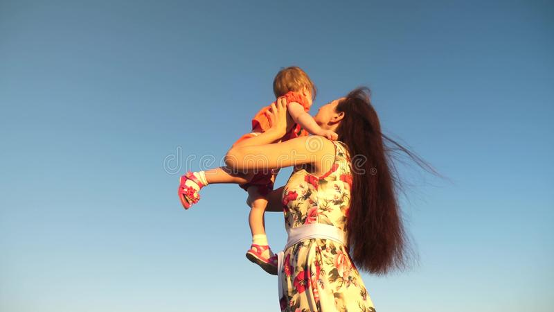 Mother throw her daughter up to blu sky. slow motion filming. Mom plays with small child in her arms against sky. happy stock images