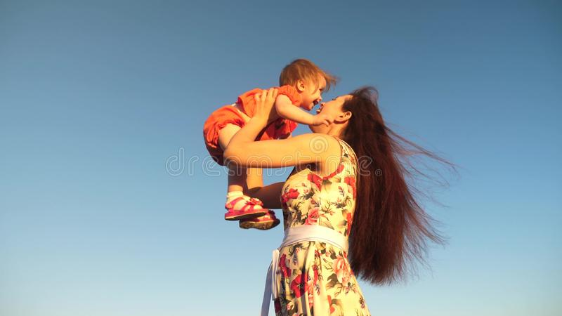 Mother throw her daughter up to blu sky. slow motion filming. Mom plays with small child in her arms against sky. happy royalty free stock photo