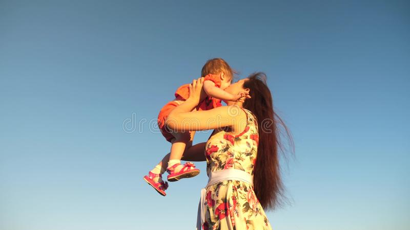 Mother throw her daughter up to blu sky. slow motion filming. Mom plays with small child in her arms against sky. happy stock image