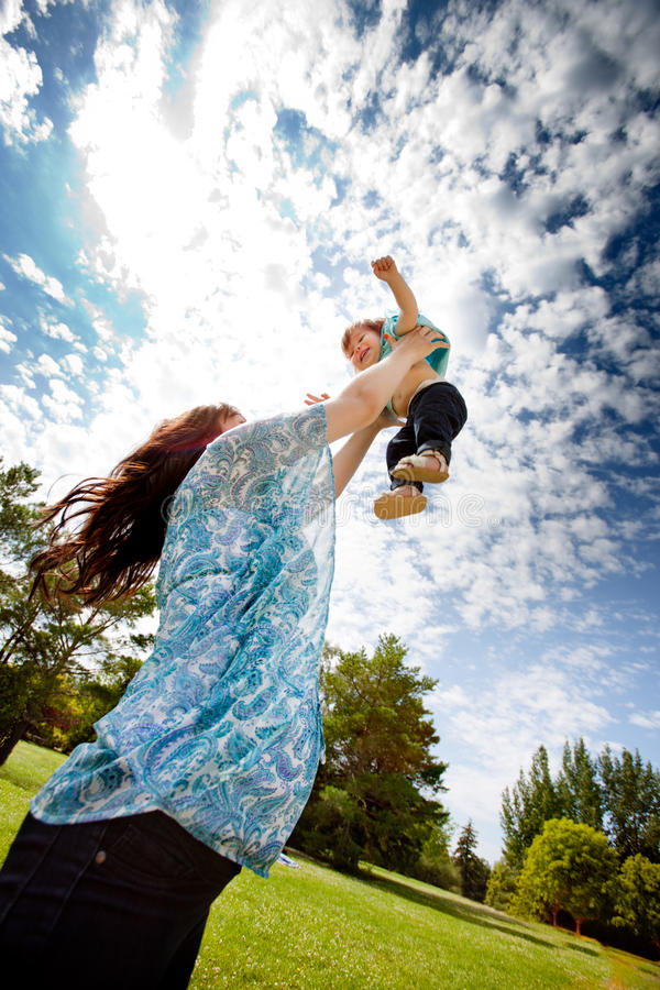 Mother Throwing Daughter in Air stock photography
