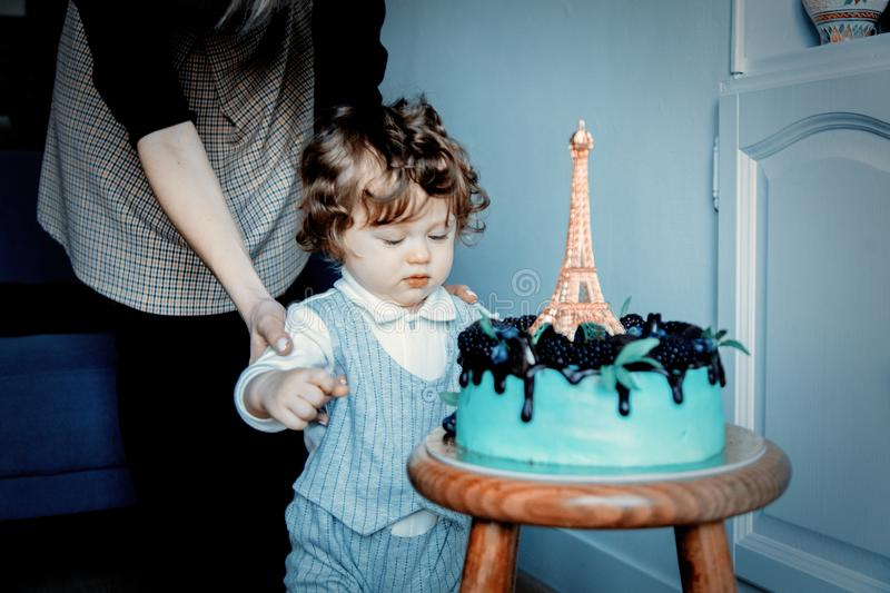 Mother and toddler boy with his first cake on Birthday. Cake is with Eiffel tower on it royalty free stock photo