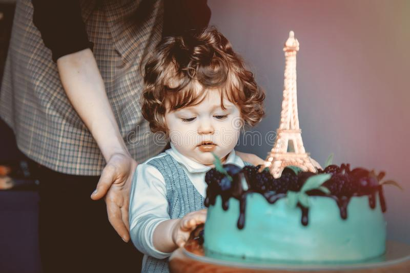 Mother and toddler boy with his first cake on Birthday. Cake is with Eiffel tower on it royalty free stock image