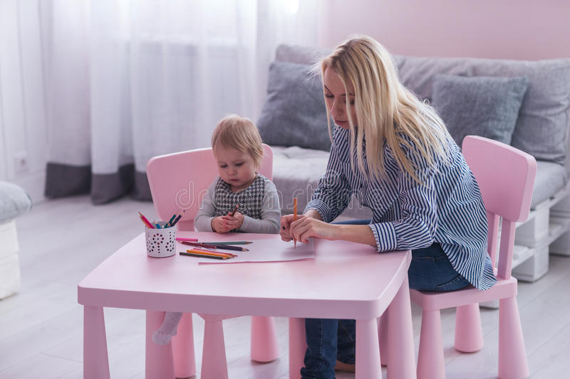Mother and toddler child drawing and painting together stock images