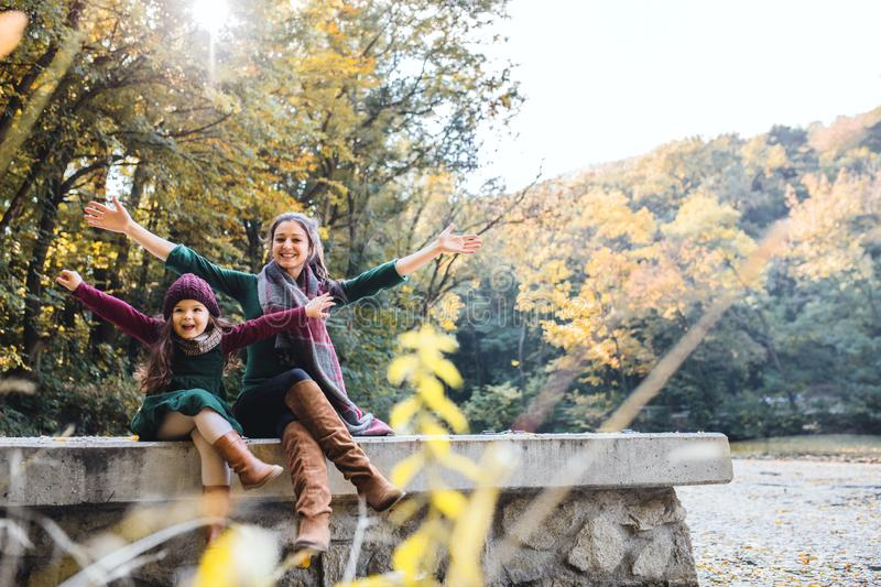 A mother with a toddler daughter sitting in forest in autumn nature, stretching arms. stock image