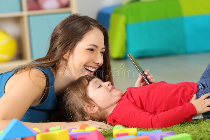 Mother and toddler playing with a smart phone stock photos