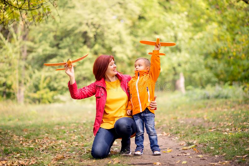 Mother and toddler son launching toy aircrafts in autumn park. Mom is kneeling, embracing her child. Dreams and travel concept stock image
