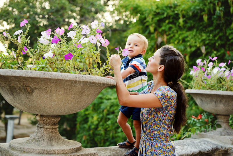 Mother and toddler son smelling flowers stock photos