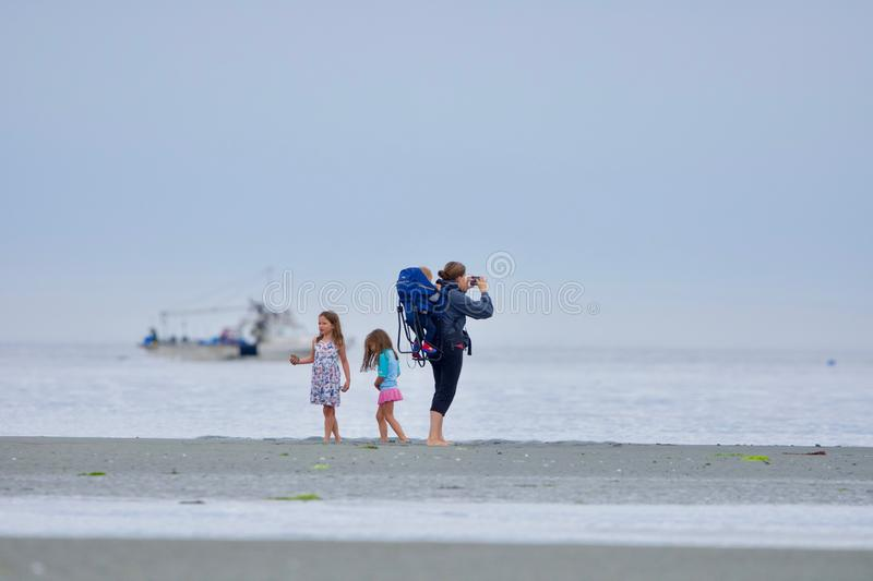 Mother with toddler and two young girls enjoy the beach at Witty`s Lagoon at low tide royalty free stock image