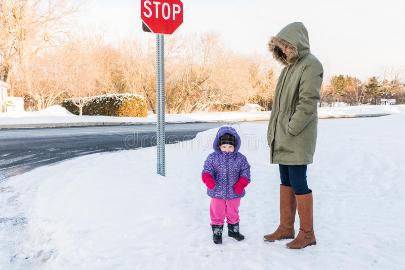 Mother and toddler wait for school bus in snow stock image