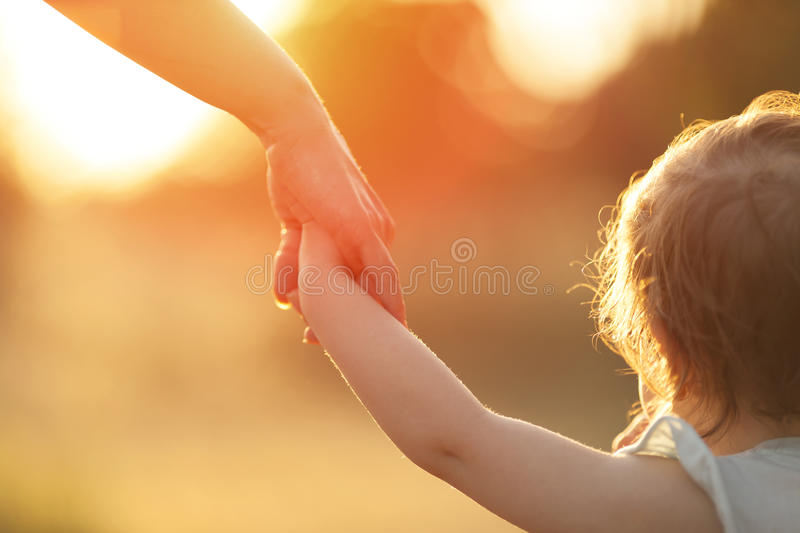Mother and toddler walking. Sunset stock image