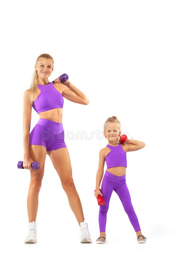Mother trainer and kid girl doing fitness exercises with dumbbells on white background. Kid doing fitness exercises at home in her room royalty free stock photography