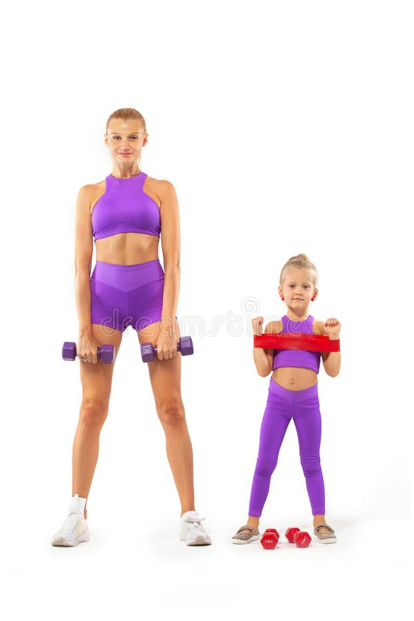 Mother trainer and kid girl doing fitness exercises with dumbbells on white background. Kid doing fitness exercises at home in her room royalty free stock images