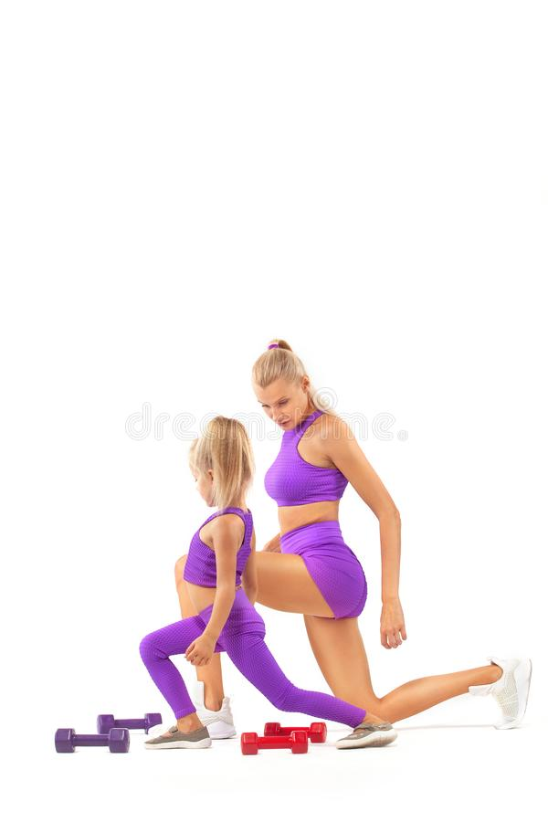 Mother trainer and kid girl doing fitness exercises with dumbbells on white background. Kid doing fitness exercises at home in her room stock photography